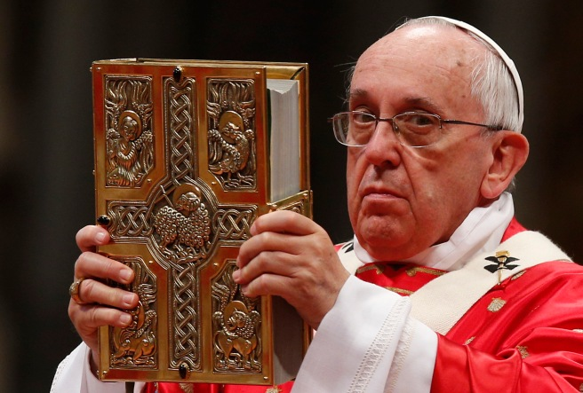 Pope Francis raises Book of Gospels during Pentecost Mass in St. Peter's Basilica at Vatican
